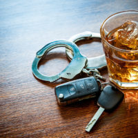 dui concept shown by keys, handcuffs, and whiskey