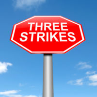 A sign that reads 3 strikes