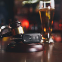concept for dui shown with keys, gavel, and drink on table